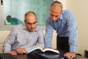בתמונה ניתן לראות את צוות המשרד קורא ומעיין בפסקי דין השונים